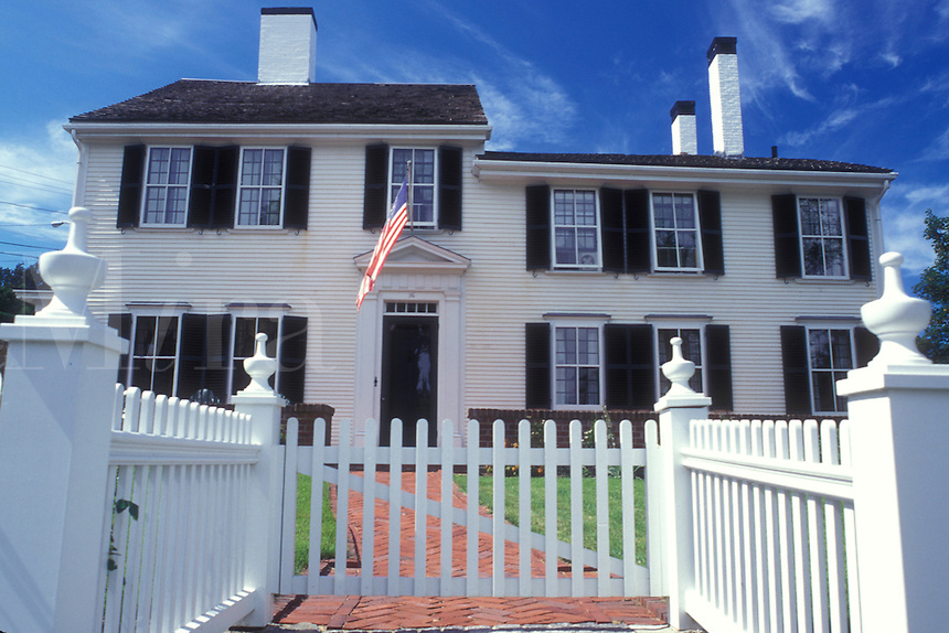Plymouth, Massachusetts, The majestic colonial white house with a white picket fence stands along the Historic Plymouth District. An American flag is hanging from the window.