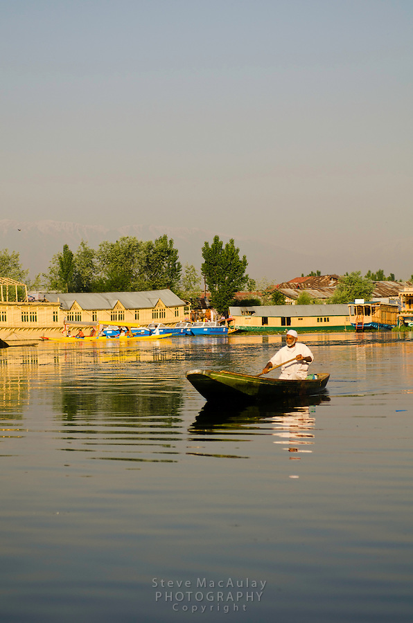 Man paddling traditional shikara on Dal Lake, Srinagar, Kashmir, India.