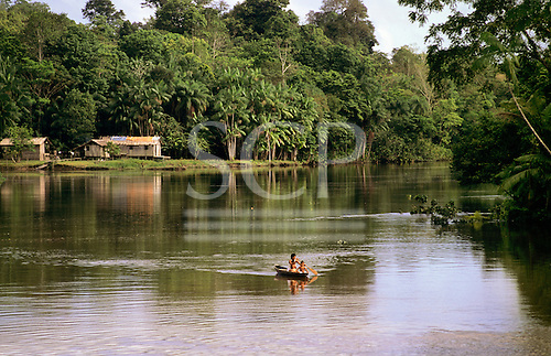 Amazon, Brazil. Riverside settlement of stilt houses with the rainforest behind; Indians on the river in a canoe.