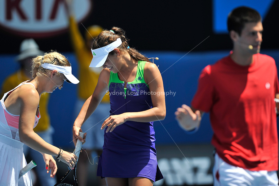 MELBOURNE, 16 JANUARY - Caroline Wozniacki helps Ana Ivanovic with her microphone at the Rally For Relief charity exhibition match by top players of the 2011 Australian Open at Melbourne Park. (Photo Sydney Low / syd-low.com)