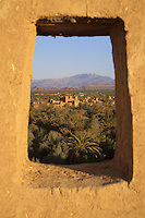 Near Skoura, Morocco - Ameridhil Kasbah Surrounded by Date Palms, Atlas Mountains in Background.
