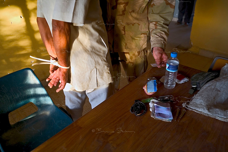 Baghdad, Iraq, June 6, 2003.A US Army officer interrogates a man arrested during an evening patrol in Thawra (ex-Saddam City), the most dangerous area of Baghdad as he was selling guns and ammunition..
