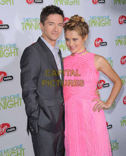 """TOPHER GRACE & TERESA PALMER.attends the Relativity Media's L.A. Premiere of """"Take Me Home Tonight"""" held at The Regal Cinemas L.A. Live Stadium 14 in Los Angeles, California, USA, March 2nd, 2011. .half length suit  grey gray shirt pink lace dress sleeveless  hand on hip.CAP/RKE/DVS.©DVS/RockinExposures/Capital Pictures."""