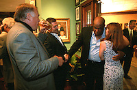 Former Green Bay Packer Willie Davis receives a vital message as he is shaking film maker Ted Demme's hand at the Lombardi Legends reunion at Lombardi's Steakhouse in Appleton, Wisconsin in September of 2001. Demme was researching the former Packers for a feature-length film but died only four months later.