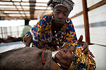 Bountouraby Camara, top, sings to her mother Fatmata Soumah, who is battling cholera at Koloma Cholera Treatment Center in Conakry, Guinea, Aug. 18, 2012. Médecins Sans Frontières is responding to a cholera outbreak in Guinea, which is affecting coastal areas and inland. Two emergency MSF cholera treatment centers in Conakry are receiving around 60 new cases per day, and a third treatment center opened over the weekend.