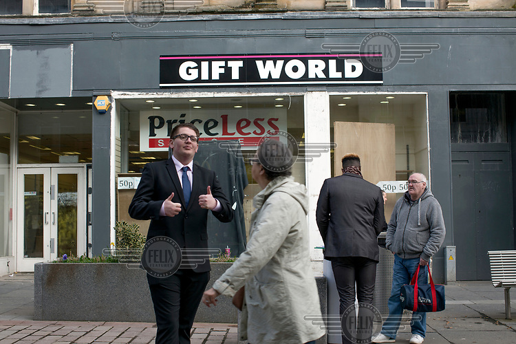 A marketer speaks to passersby on Paisley's high street which hosts many empty and second-hand shops reflecting the town's economic decline.