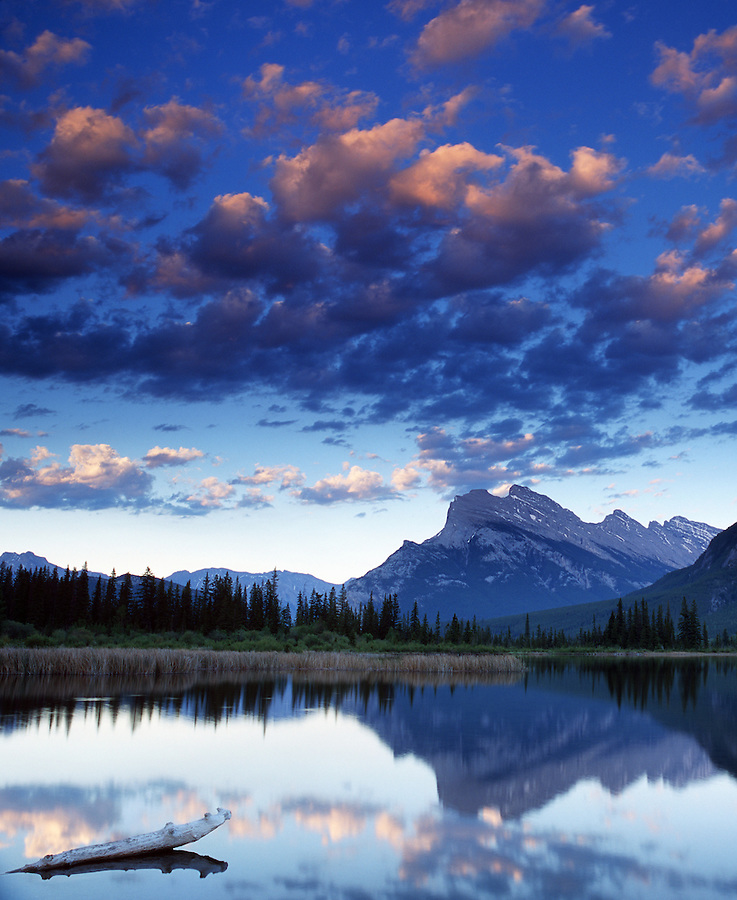 Warm light highlights the altocumulus clouds flying high above Mount Rundle as seen from the Vermillion Lakes area of Banff National Park in Alberta, Canada.