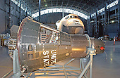 Chantilly, VA - December 11, 2003 -- Two different generations of United States manned spacecraft, the Mercury 10 and the Space Shuttle Enterprise are photographed together inside the still incomplete space hanger at the Steven F. Udvar-Hazy Center in Chantilly, Virginia on December 11, 2003.  The Mercury 10 is the only surviving intact flight-ready Mercury spacecraft.  The Enterprise was the first space shuttle built.  It was designed to test facilities and landing systems, but not to fly in space..Credit: Ron Sachs / CNP.(RESTRICTION: NO New York or New Jersey Newspapers or newspapers within a 75 mile radius of New York City)