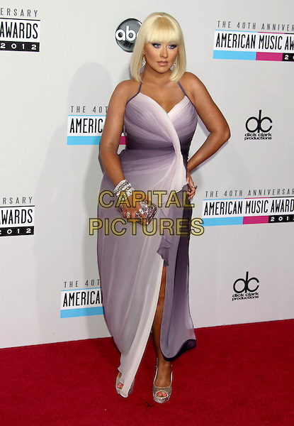 Christina Aguilera.40th Anniversary American Music Awards - Arrivals held at Nokia Theatre L.A. Live, Los Angeles, California, USA..November 18th, 2012.AMA AMAs full length purple white wrap dress slit split clutch bag hand on hip .CAP/ADM/RE.©Russ Elliot/AdMedia/Capital Pictures.