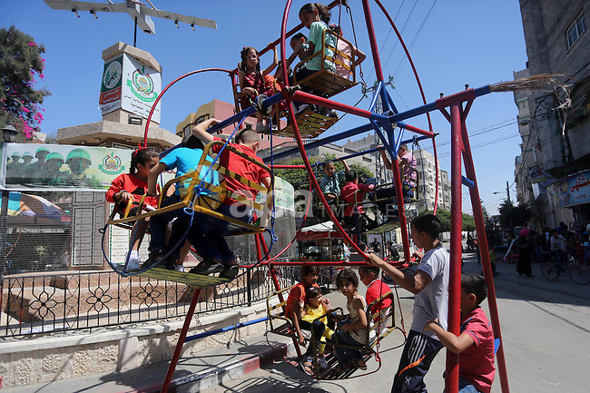 Palestinian children enjoy a ride at an amusement park during the third day of Eid al-Adha or the feast of sacrifice, in Gaza city, on Sep. 14, 2016. Muslims across the world are celebrating the annual festival of Eid al-Adha, or the Festival of Sacrifice, which marks the end of the Hajj pilgrimage to Mecca and in commemoration of Prophet Abraham's readiness to sacrifice his son to show obedience to God. Photo by Mohammed Asad