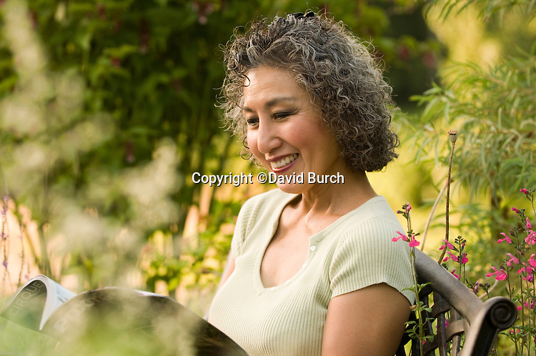 Asian woman reading a magazine and relaxing in her garden