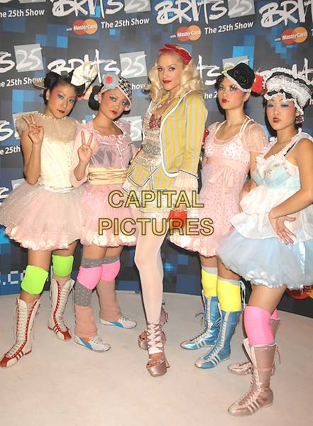 GWEN STEFANI & DANCERS.Brit Awards 2005.Earls Court 2, London, .February 9th 2005..full length holding award trophy red leather gloves hair band headband hairband bow girls.Ref: DH.www.capitalpictures.com.sales@capitalpictures.com.©David Hitchens/Capital Pictures .
