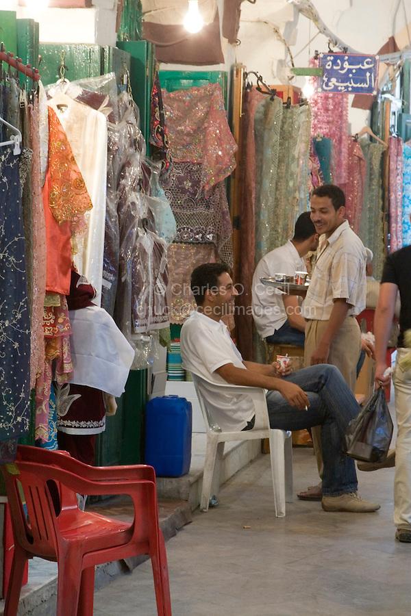 Tripoli, Libya. Medina, Clothing and Fabric Suq, Waiter Serving Coffee.