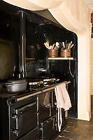 A black enamel Aga stands comfortably in the massive inglenook fireplace