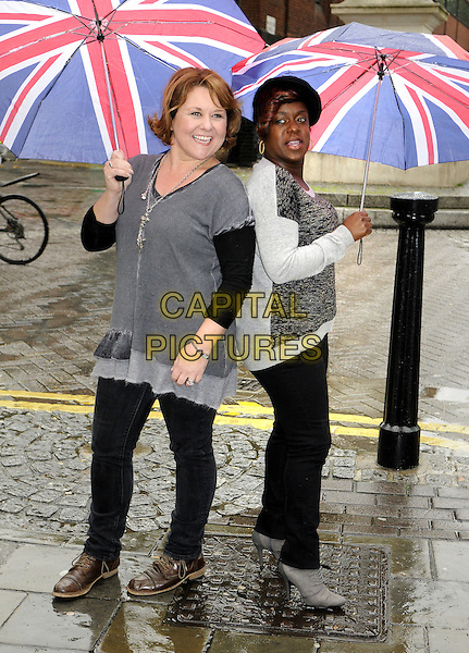 Wendi Peters, Tameka Empson.'Our House' Photocall outside the Cambridge Theatre, London to announce the 10th Anniversary West End gala concert at the Savoy Theatre in aid of Help for Heroes, London, England, October 19th 2012..full length suit umbrella raining grey gray  top jeans back to back  jumper .CAP/BK/PP.©Bob Kent/PP/Capital Pictures