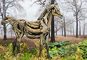 Sunday, 19 May 2013, London, UK. Planting and set-up work continues for the Chelsea Flower Show 2013 ahead of its opening next Tuesday. Pictured: a wooden horse in front of a forest background.
