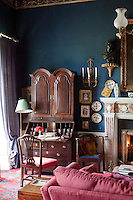 A Georgian bureau in one corner of the living room stands out against the royal blue wall