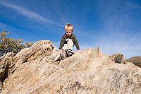 3 year old boy climbing rocks in the Sonoran Desert, Arizona (MR)