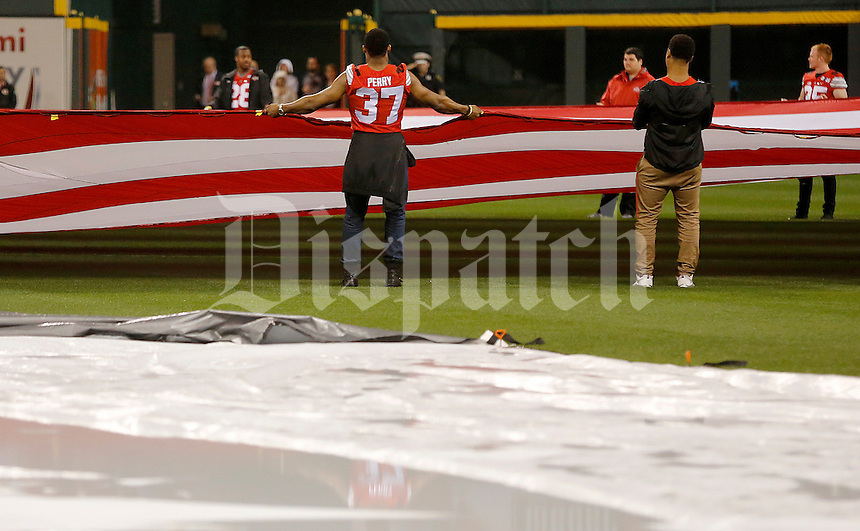 Ohio State linebacker Joshua Perry helps hold the flag prior to the Cincinnati Reds game against Pittsburgh at Great American Ball Park on Wednesday, April 8, 2015. (Columbus Dispatch photo by Jonathan Quilter)