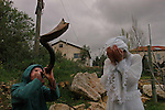 Settlers- a kid blowing a ram's horn and a woman praying, during a party for the Jewish holiday of Purim, in the Israeli settlement of Elazar, West Bank.