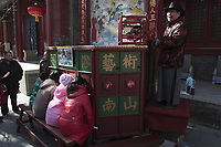 """Chinese children watch a display of traditional drawings from Chinese myths as an artist dressed in traditional costume sings to illustrate the stories at a traditional mobile """"theatre"""" at a temple fair to celebrate the Lunar New Year of the Tiger on February 15, 2010 in Beijing, China. The Chinese characters read """"Folk Art""""."""