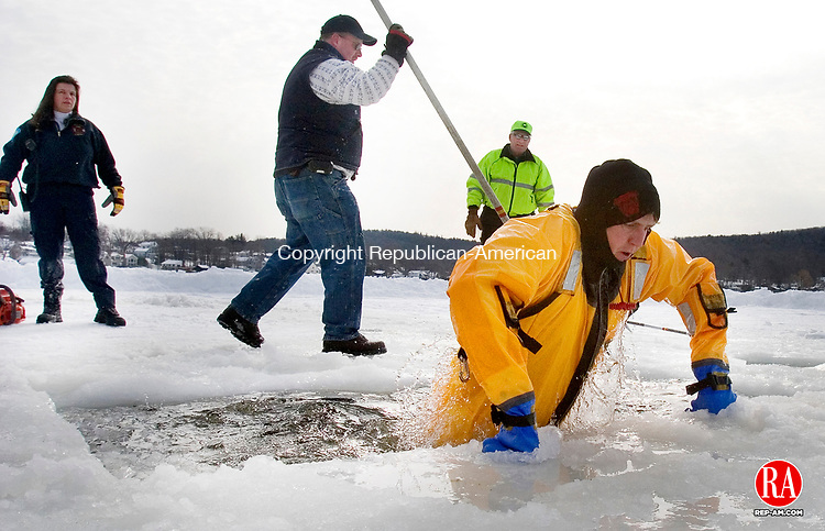 WINSTED, CT 06 February 2008-020609SV01--Firefighter Donovan Brown kicks large chucks of ice under the ice-covered lake while clearing a space for sixth annual Highland Lake Penguin Plunge to benefit Special Olympics Connecticut Northwest Region Friday in Winsted. The plunge will be held Saturday.<br /> Steven Valenti Republican-American