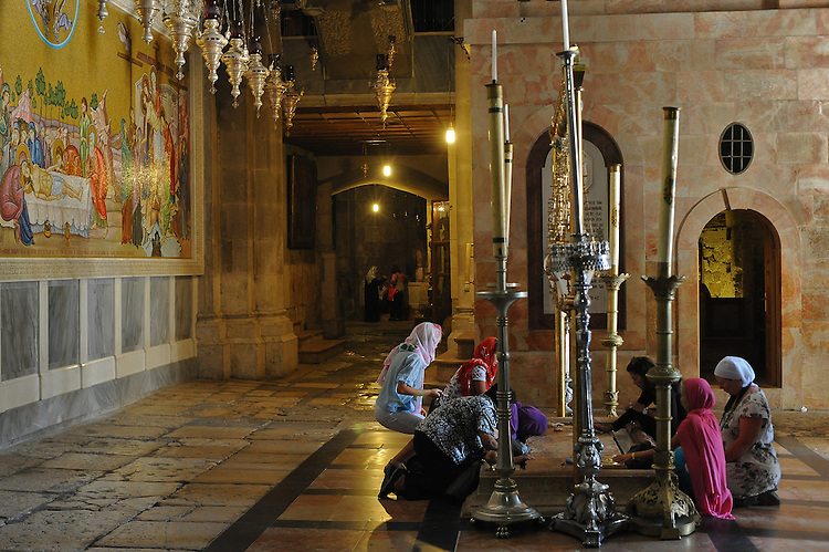 Women pilgrims pray on the Stone of Anointing, on which Jesus Christ is said to have been smeared with oil after being crucified, at the Church of the Holy Sepulchre in Jerusalem's old city, Israel. The church sits on the site where Jesus Christ is believed to have been crucified and buried.