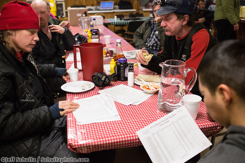 With the race standings in hand, Aliy Zirkle, Aaron Burmeister, Allen Moore and Mike Williams Jr. talk race strategy at the Takotna checkpoint during their 24 hour layover on Wednesday March 6, 2013...Iditarod Sled Dog Race 2013..Photo by Jeff Schultz copyright 2013 DO NOT REPRODUCE WITHOUT PERMISSION