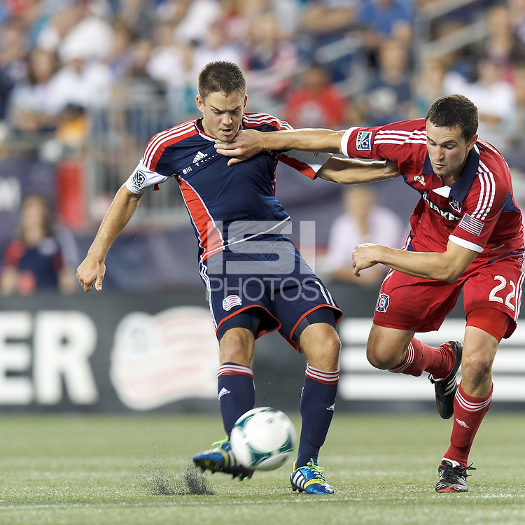 New England Revolution midfielder Kelyn Rowe (11) takes a shot as Chicago Fire defender Austin Berry (22) defends. In a Major League Soccer (MLS) match, the New England Revolution (blue) defeated Chicago Fire (red), 2-0, at Gillette Stadium on August 17, 2013.