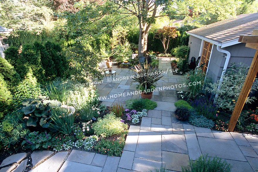 A flagstone patio surrounded by lush plantings creates a private space for outdoor living.