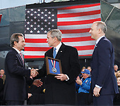 New York, NY - November 11, 2008 -- Charles de Gunzburg watches United States President George W. Bush shake hands with Richard Santulli (L) after President Bush receives the Intrepid Freedom Award at the rededication ceremony of the Intrepid Sea, Air and Space Museum in New York City on Tuesday, November 11, 2008. <br /> Credit: John Angelillo - Pool via CNP