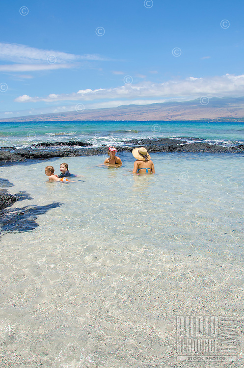 A local boy and girl play while their mothers converse in a tidal pool at a beach in Puako, South Kohala, Big Island of Hawai'i.
