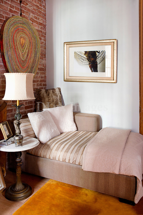 Chaise lounge in living room with exposed brick wall