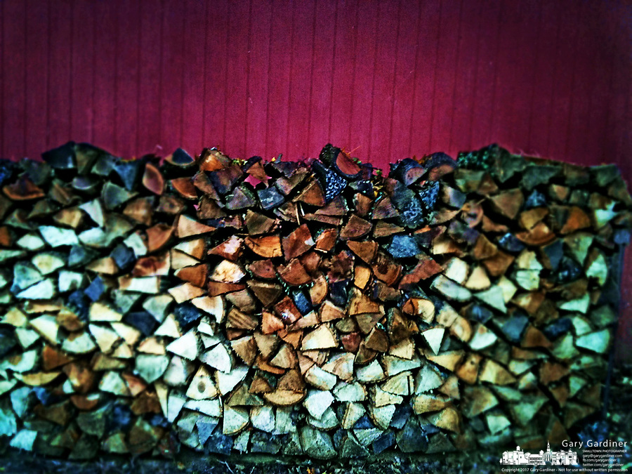 Cord of split and dried wood lined up and stacked against red wall at edge of house.