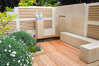 Garden ornament against modern wall, deck patio, Dianthus mounds, bench, decorated like an outdoor room with sense of enclosure and privacy, backyard deck landscaping, water feature with arc of spray