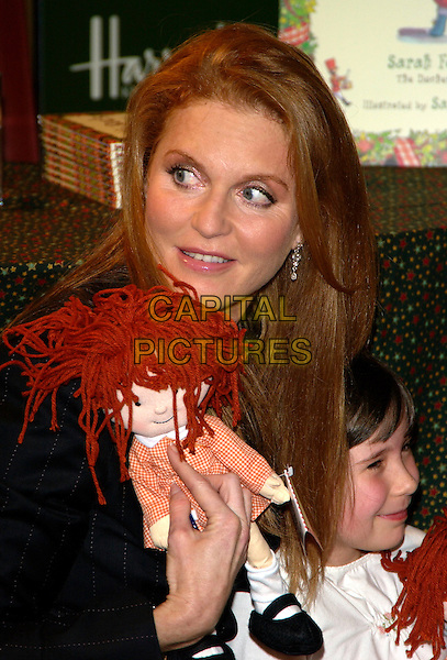 """SARAH FERGUSON, Duchess of York.Signs copies of her new book """"Little Red's Christmas Story"""" ,Harrods , London 28  October 2004..portrait headshot doll.Ref: PL.www.capitalpictures.com.sales@capitalpictures.com.©Capital Pictures.."""