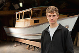 USA, Alaska, Homer, 16 year old Ben Fetterhoff stands in front of a 24 foot fishing boat that he is building, at his home in Homer