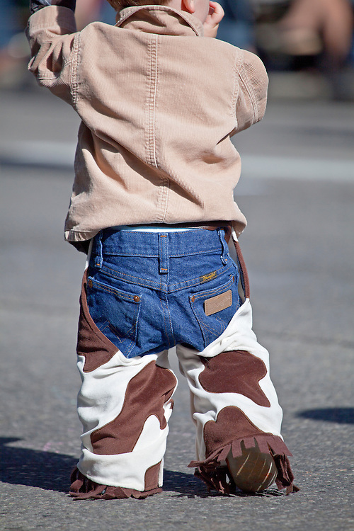 Young boy wears homemade cowboy chaps during the Calgary Stampede parade in Calgary, Alberta, Canada