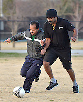 STAFF PHOTO BEN GOFF  @NWABenGoff -- 12/25/14 Sudheesh Vasudevan, left, and Pramod Ramachandran of Bentonville go after the ball while playing in a pickup soccer game at Memorial Park in Bentonville on Thursday Dec. 25, 2014.