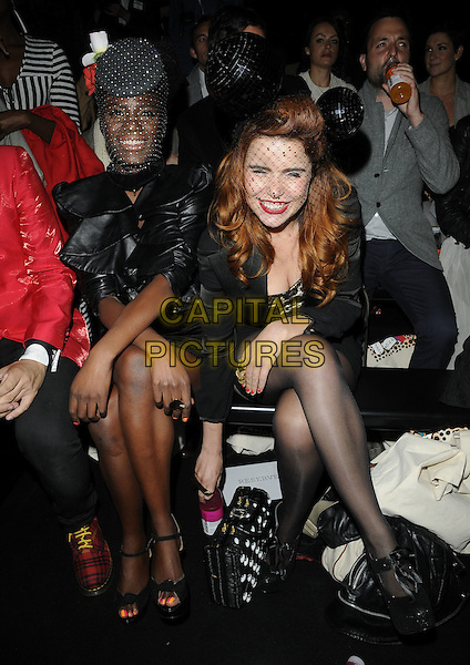 SHINGAI SHONIWA & PALOMA FAITH .At the PPQ Fashion show during Day 1 of London Fashion Week, BFC Catwalk Show Space, Somerset House, London, England, UK, September 17th 2010..LFW full length black jacket netting net hat ears mickey mouse holding hands  playsuit shorts sitting down  ruffles smiling disco balls .CAP/CAN.©Can Nguyen/Capital Pictures