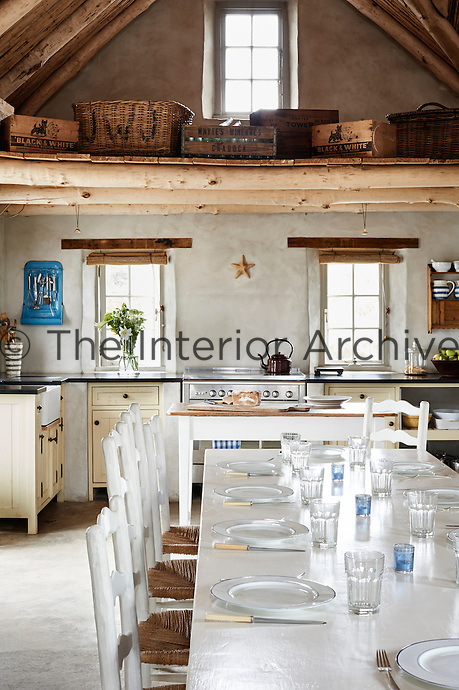 A spacious country kitchen with a timber ceiling. Baskets and boxes are arranged in the roof space above a white  painted table set for lunch.