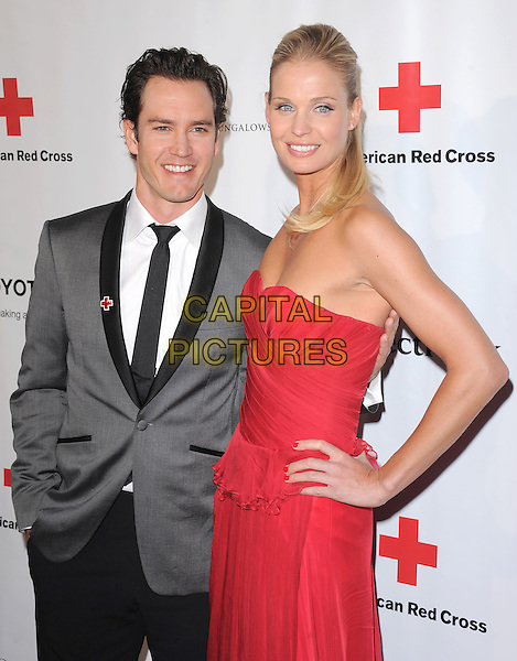 MARK PAUL GOSSELAAR & wife .At The American Red Cross, Santa Monica Chapter's Annual Red Tie Affair held at The Fairmont Miramar Hotel & Bungalows in Santa Monica, California, USA, April 9th 2011..half length red strapless dress jacket suit  black tie white shirt grey gray couple                                                        .CAP/RKE/DVS.©DVS/RockinExposures/Capital Pictures.