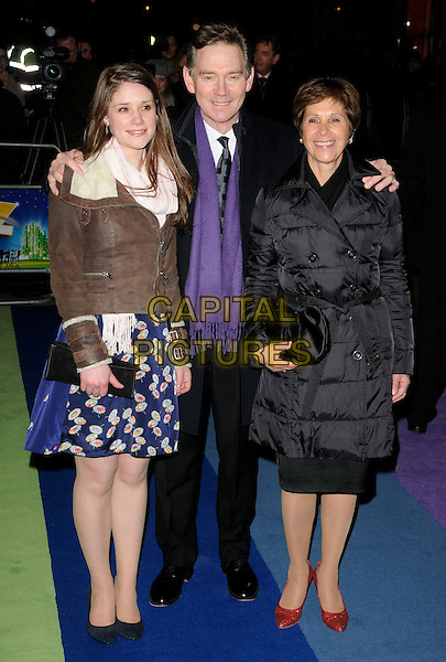 "ANTHONY ANDREWS & FAMILY .At  ""The Wizard Of Oz"" Press Night, London Palladium, London, England, UK, March 1st 2011..full length daughter wife purple scarf tie arms around black coat brown jacket suit .CAP/CAN.©Can Nguyen/Capital Pictures."