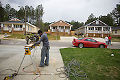 Builders For Hope crew member Saqoya Pryor works a chop saw in front of a trio of home that have be relocated and repaired to populate the Barrington Village development in South-East Raleigh, Tues., April 14, 2009. .