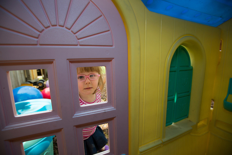 Marianne peeks into her toy house in the back yard. Quieter than her triplet siblings, she mostly keeps to herself.