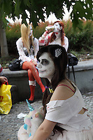 Young woman photographed in Profile, wearing zombie make up, a white dress and holding a Unicorn toy while waiting for the Zombie walk to start. Behing 2 other female participants in the Zombie Walk sitting.