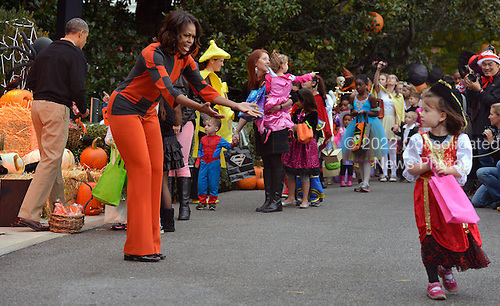 First lady Michelle Obama (C) holds out her hands to a child who missed getting candy as she and United States President Barack Obama (L) welcome treat-or-treating local children and children of military families, to the South Portico of the White House, to celebrate Halloween, October 31, 2013, in Washington, DC.    <br /> Credit: Mike Theiler / Pool via CNP