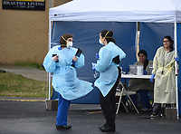 Tracy Sanchez (left), director of nursing at Community Clinic, and nurse practitioner Holly Rogers discuss directions Wednesday, March 18, 2020, for visitors at the Wellness Center at Elmdale Elementary School testing and treatment site for the covid-19 in Springdale. New sites opened at Prairie Grove Elementary School, the Rogers Community Clinic, Siloam Springs Community Clinic and the Springdale location. Washington Regional Medical Center in Fayetteville opened its covid-19 screening clinic Monday. Check out nwaonline.com/200319Daily/ and nwadg.com/photos for a photo gallery.<br /> (NWA Democrat-Gazette/David Gottschalk)