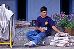 Young boy (9-10 yrs old) preparing papers for his paper route