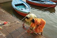 woman during morning prayer (puja) at river Ganga, Varanasi